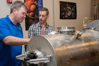 Professor Chris Dreyer works with a student in the Center for Space Resources lab