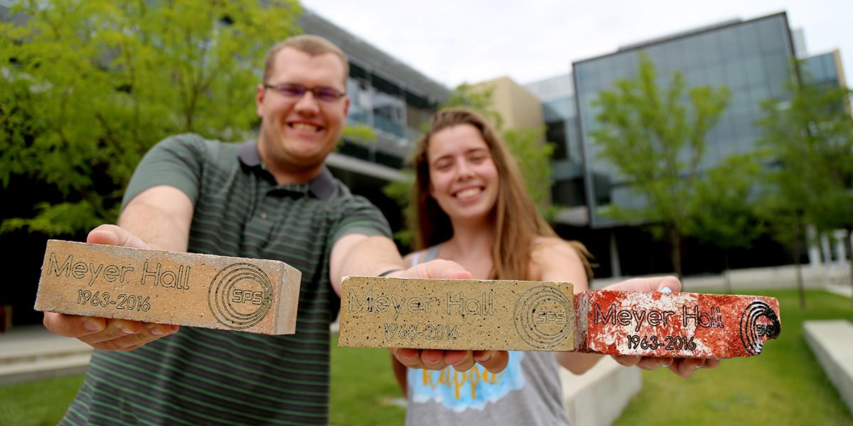 David Schmidt and  Lindsey Hart hold Meyer Hall bricks