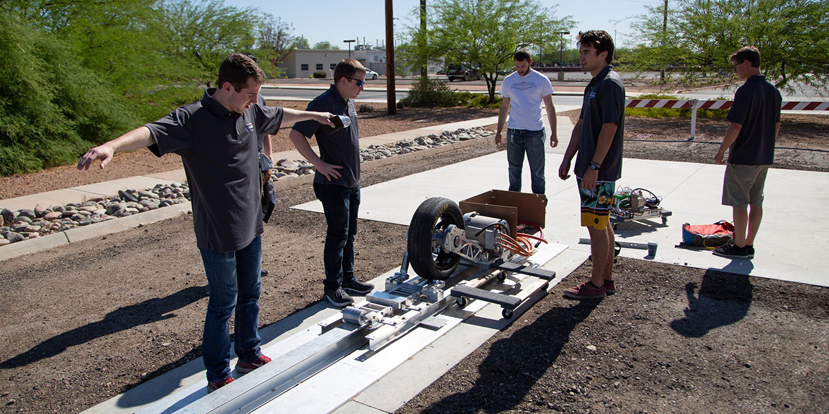DiggerLoop team members size up their pod on the test track at Arizona State University