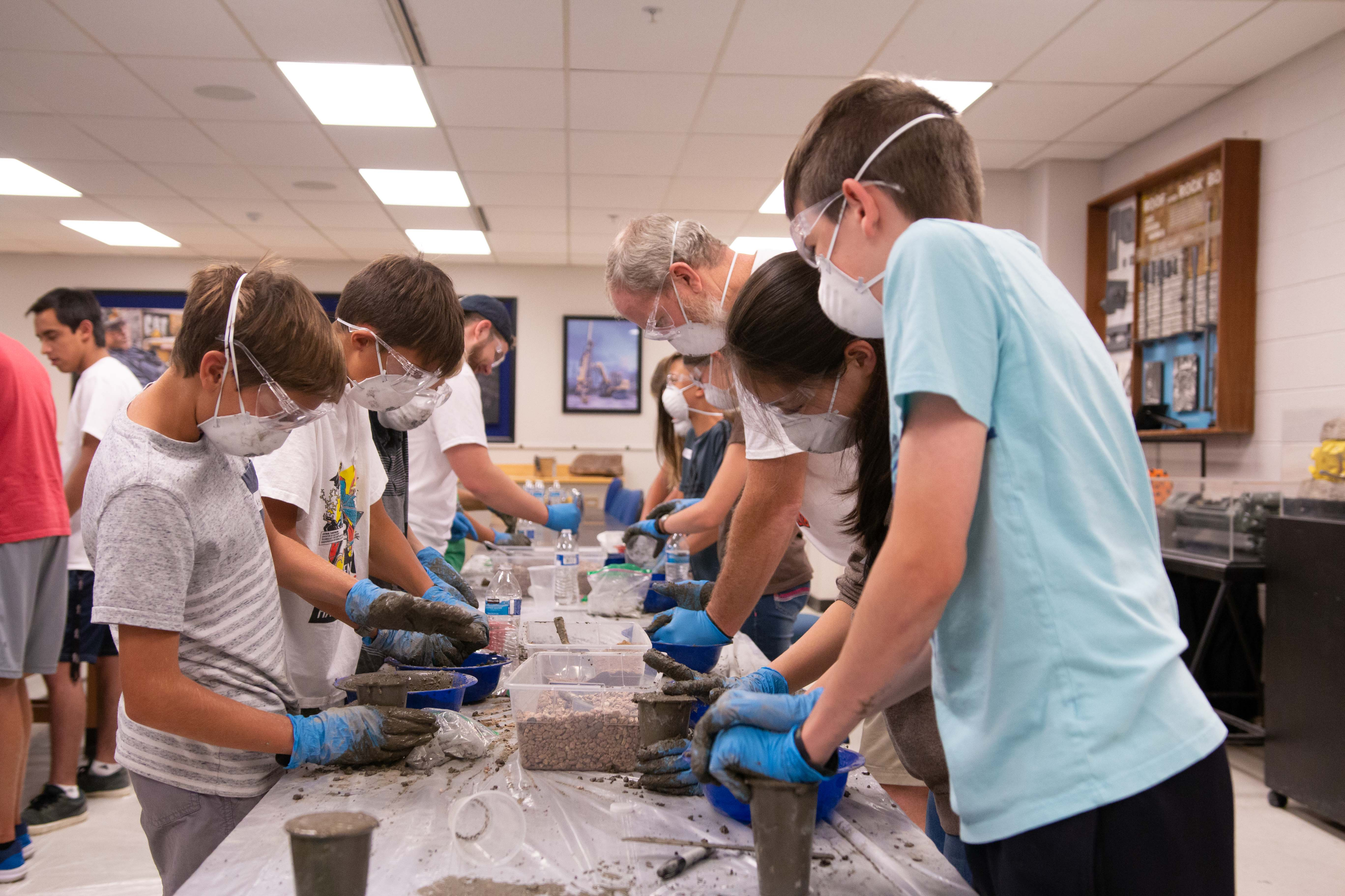 Students mix concrete at Tunnel Camp