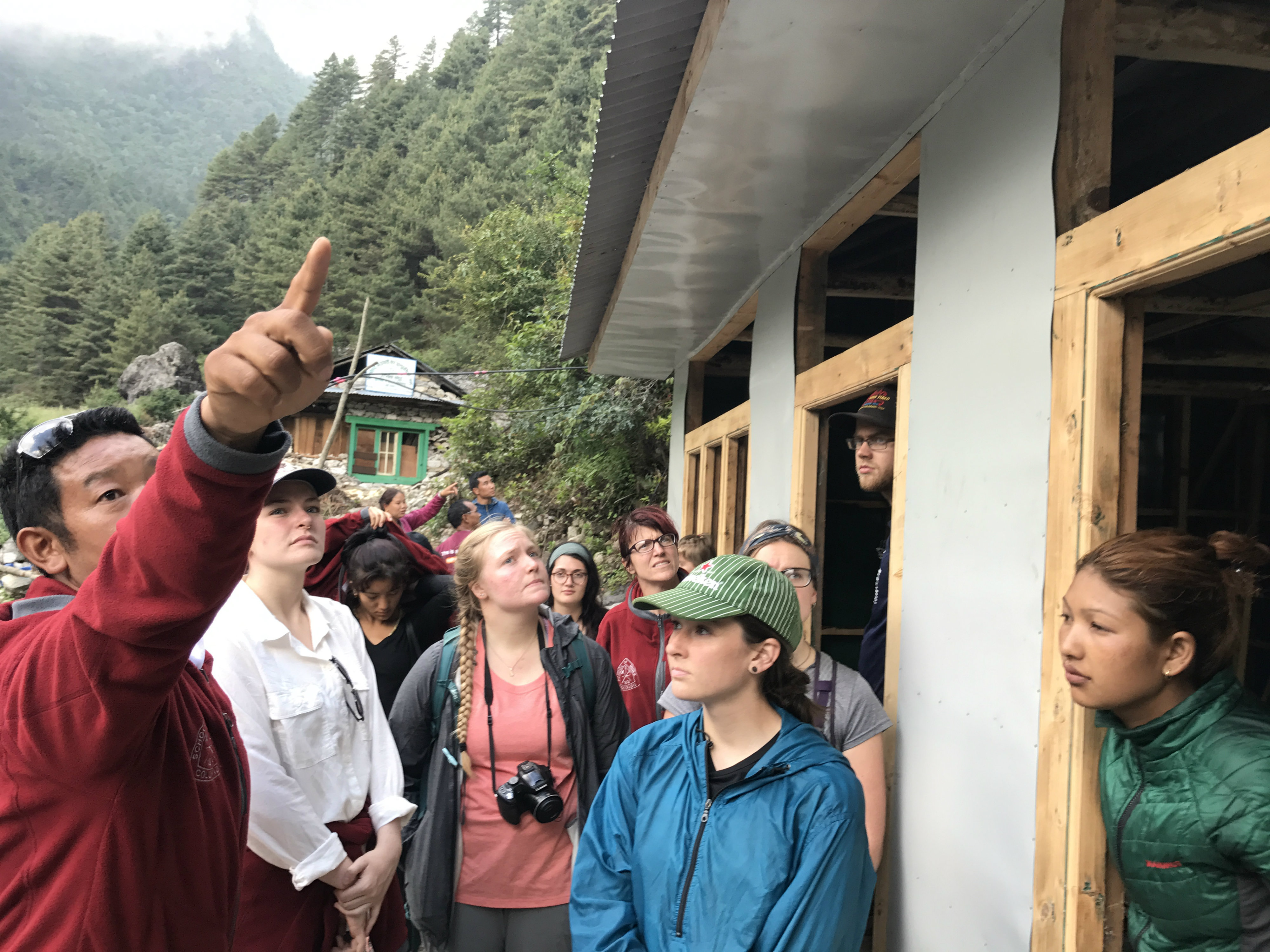 Lhakpa Sherpa, founder of Hike for Help, explains to Mines students the construction of Hike for Help's workshop for the Dalit to produce and sell their handicrafts .