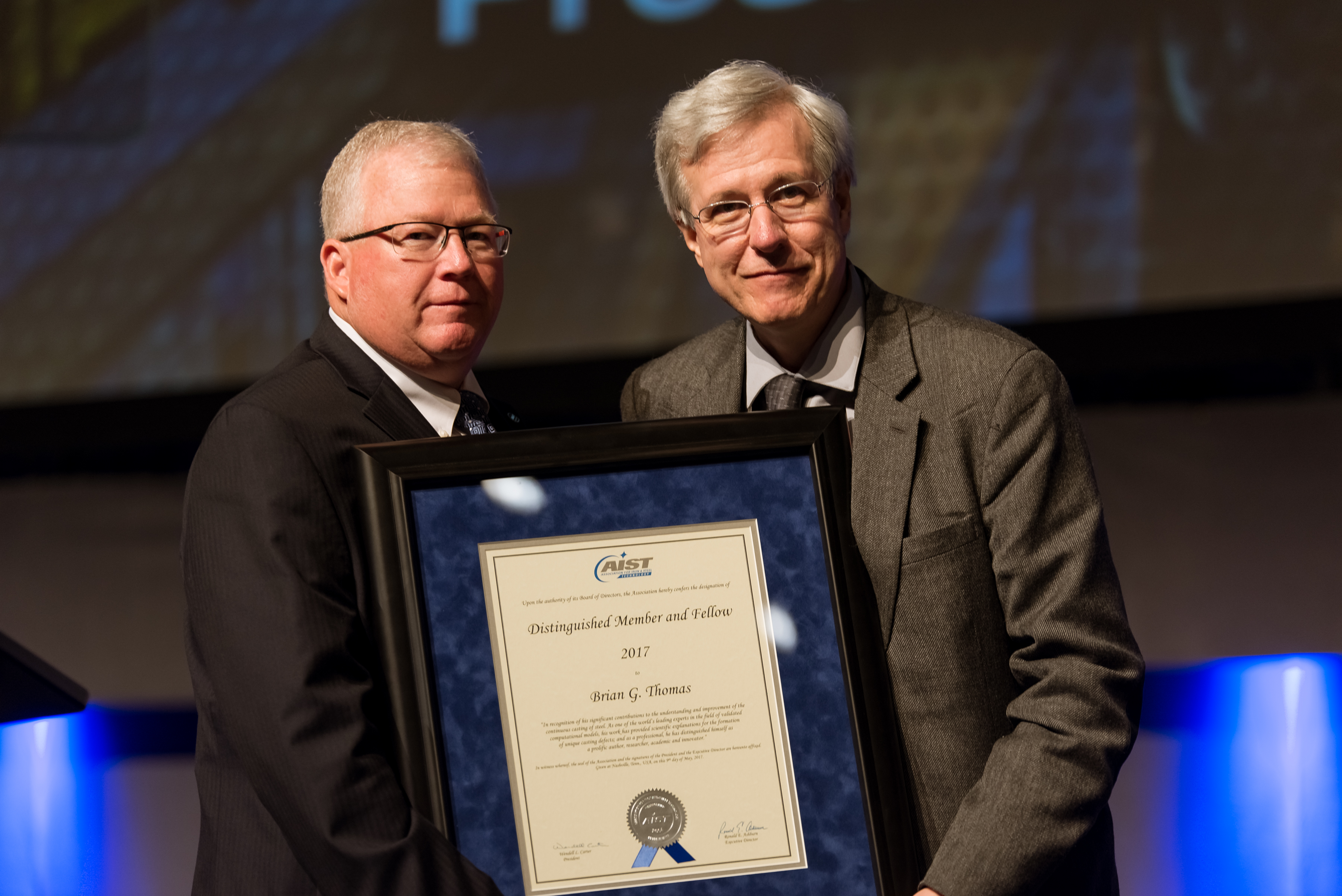 AIST Past President Wendell Carter, left, presents the Distinguished Member and Fellow Award to Brian Thomas.
