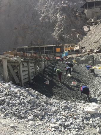 Workers at a small mine in Secocha, Peru pick through waste rock as they look for ore-rich pieces. Photo by Paul Santi
