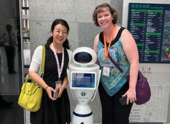 CUMT librarian Jie Bao shows Brianna Buljung a robot they use in their library.