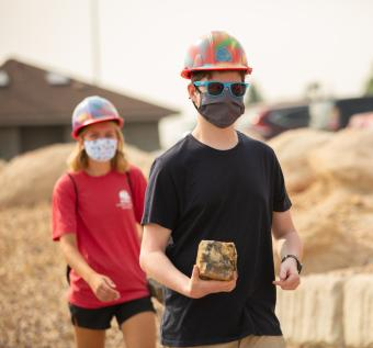 Two Mines students carry rocks to temporary M