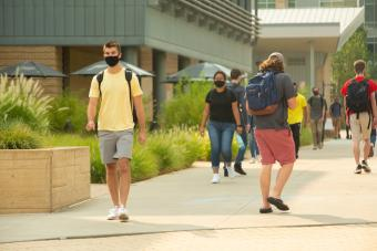 Masked students walk on pedestrian mall