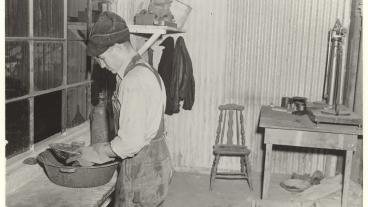 A man wearing overalls performs a pan test in a rough laboratory.