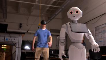 Student works with a humanoid robot in Xiaoli Zhang's lab
