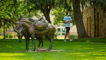 Masked student walks by A Friend to Lean on statue
