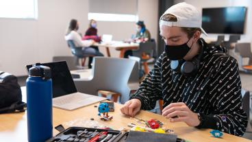 Masked student works on project in the new McNeil Hall