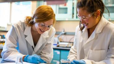 Two female students work in a lab