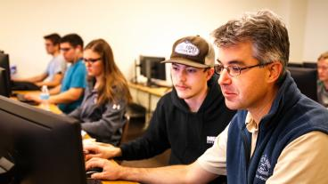 Paul Sava, right, works with a student during a Linux lab class