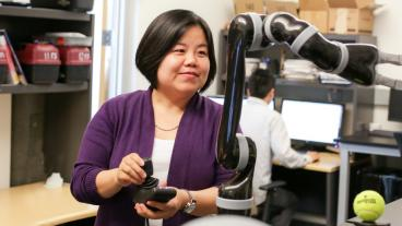 Xiaoli Zhang operates a robotic arm in a lab at Mines