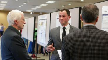 Dean Kevin Moore and another judge listen to a poster presentation.
