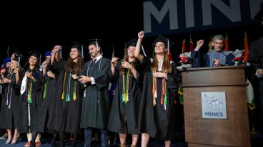 Jennifer Kendall and her fellow student athletes lead the Mines fight song at commencement