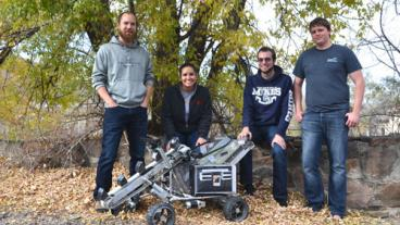 Seniors Marc Allen, Megan Salinas, Ryan Stauffer and Kevyn Young pose around the lunar mining rover.
