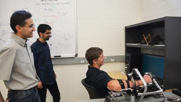 From left, mechanical engineering professor Ozkan Celik and graduate student Hossein Saadatzi watch as student David Long demonstrates the Wrist Gimbal.