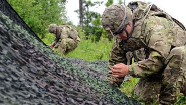 U.S. Army soldiers  weave cords through the camouflage net in order to keep their radar and area of operation concealed