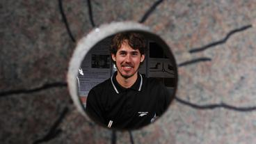PhD student Luke Frash is seen through a cross-section of a fractured granite specimen.