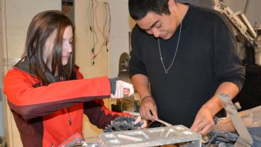 Mechanical engineering student Kaitlyn Martin and electrical engineering student Eduardo Urquidi Junior are taking apart last year's rover.
