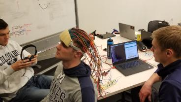 Students testing headpiece with infrared emitters and sensors
