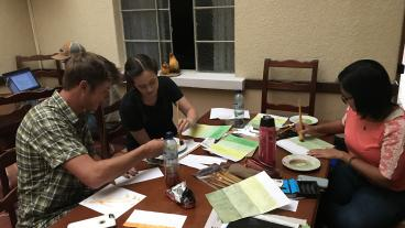 Mines students Jake Weems, Lindsay Hoylman and Vy Duong prepare for field work by painting and drawing items to assist in the interview process.