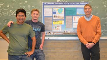 Applied physics graduate student Carlos Medina, engineering physics junior Steven Hackenburg and physics professor Dr. Lawrence Wiencke. The poster in the background shows the laser facility at the Pierre Auger Observatory used in this project.