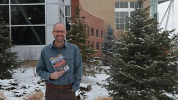 "Kenneth Osgood, associate professor and director of the McBride Honors Program, holds his new book, ""Winning While Losing: Civil Rights, the Conservative Movement and the Presidency from Nixon to Obama"" on Mines campus."