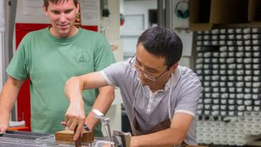Brandon Dugan (Co-Chief Scientist, Colorado School of Mines, USA) watches Tao Yang (Paleomagnetist, Institute of Geophysics, China Earthquake Administration, China) at the core sampling table. (Credit: Tim Fulton, IODP-JRSO)