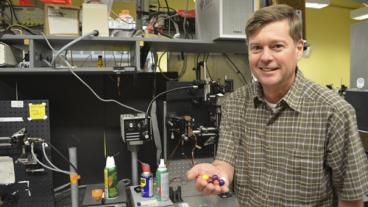 Chemical and biological engineering department head Dr. Dave Marr holds microbot models.