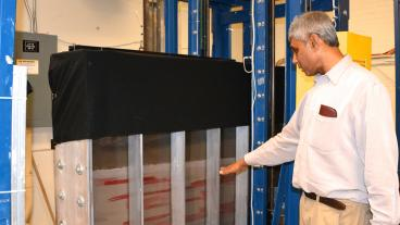 Civil and Environmental Engineering professor Tissa Illangasekare motions toward one of the larger tanks that he uses to study soil concentrations.
