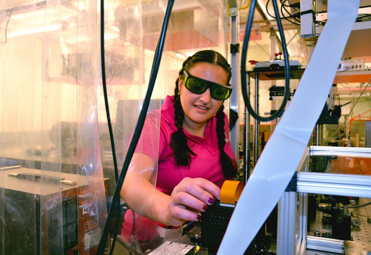 PhD student Alyssa Allende Motz inspects a machine in the engineering physics lab at Mines.