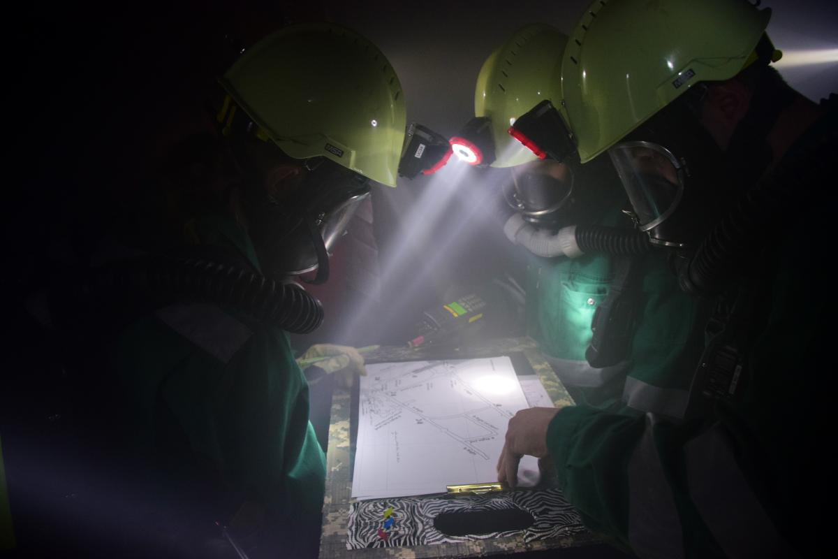 A team looks at a map to find and rescue a victim during the field competition at the Edgar Mine.