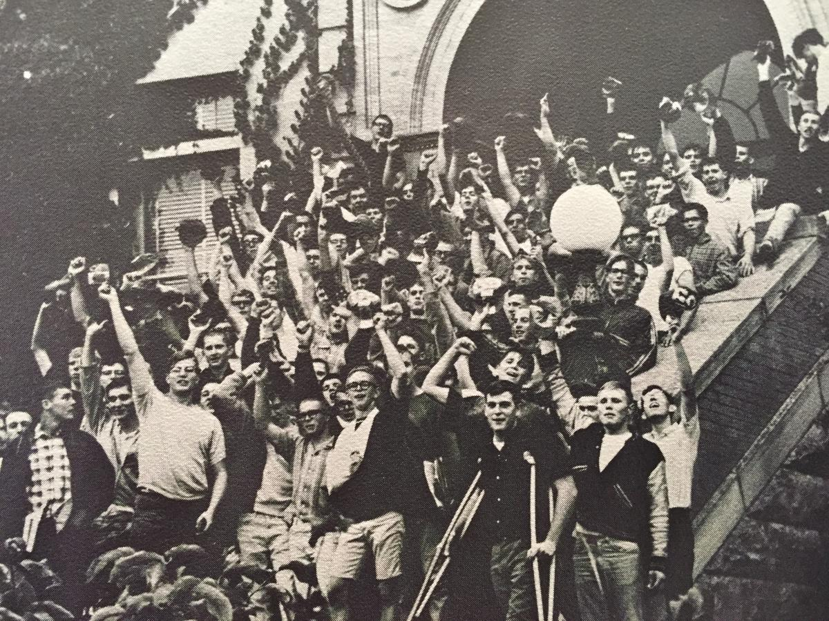Black and white photo of the 1966 freshman class celebrating in front of one of the buildings on the Mines campus