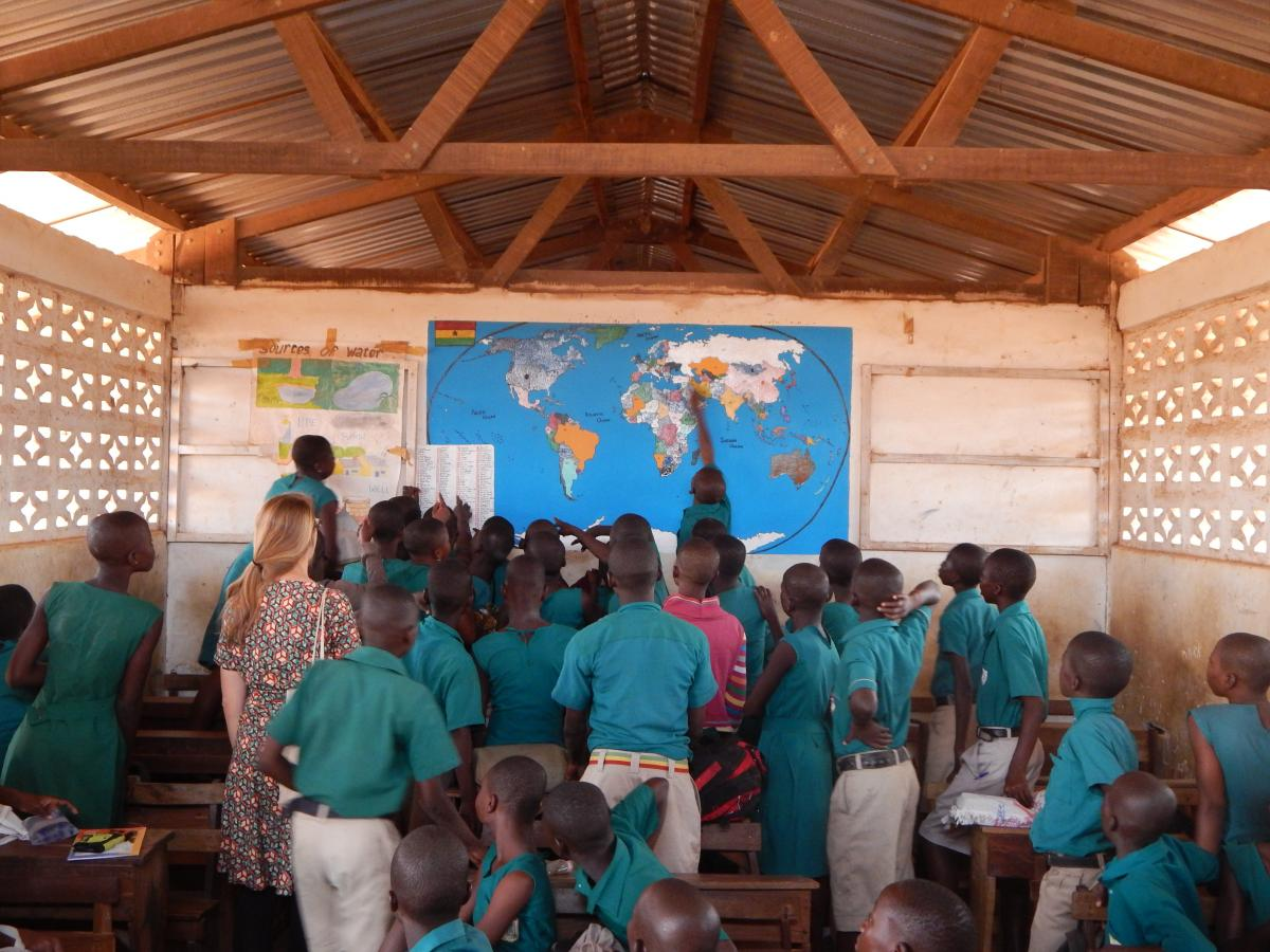 Ghanaian students point to a map on a classroom wall