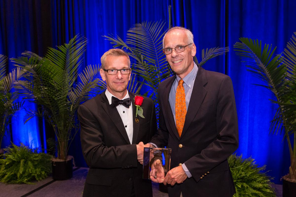 SEG President John Bradford presents Roel Snieder with the Outstanding Educator Award at the 2016 annual meeting in Dallas.