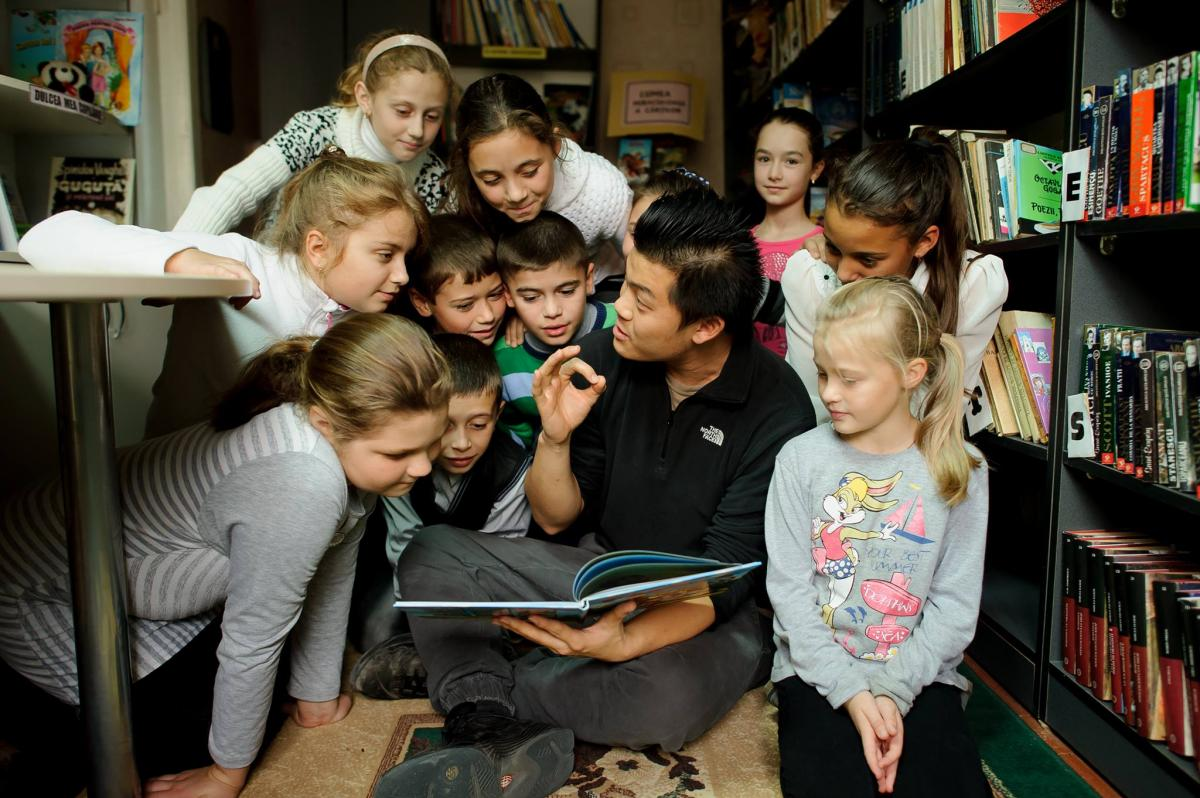 Peace Corps volunteer reads books to children in Moldova.