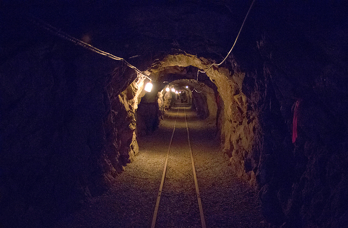 A view into a deep mining tunnel with tracks running down the middle.